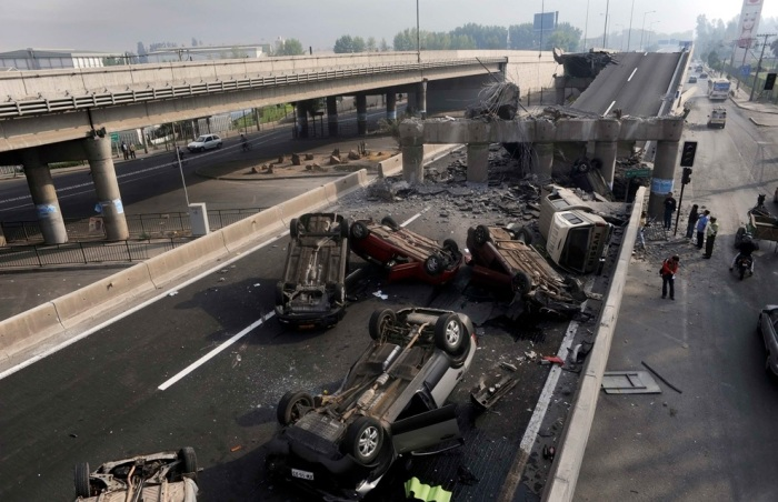 Cars lie overturned after the highway they were travelling on was destroyed in an earthquake in Santiago February 27, 2010. (REUTERS/Marco Fredes)